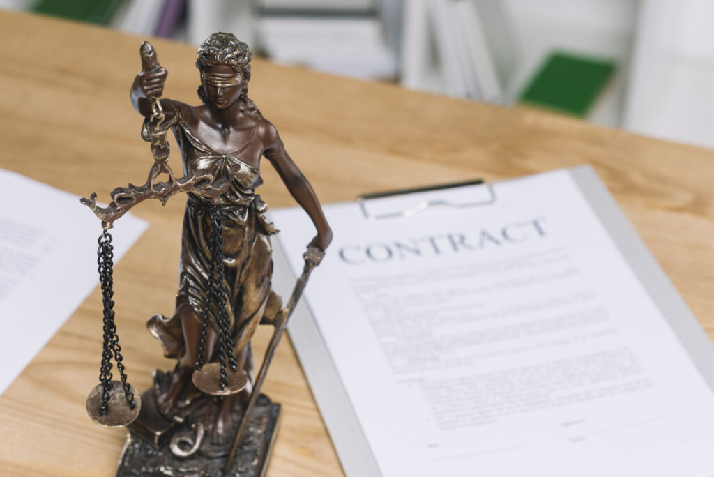 statue justice table with contract paper